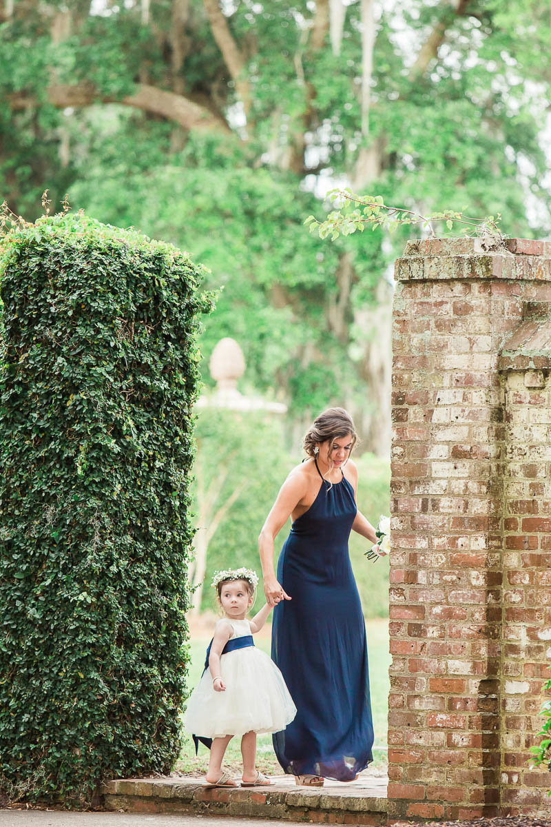 Flower girl steps into the garden, Dunes West Golf and River Club, Mt Pleasant, South Carolina. Kate Timbers Photography.