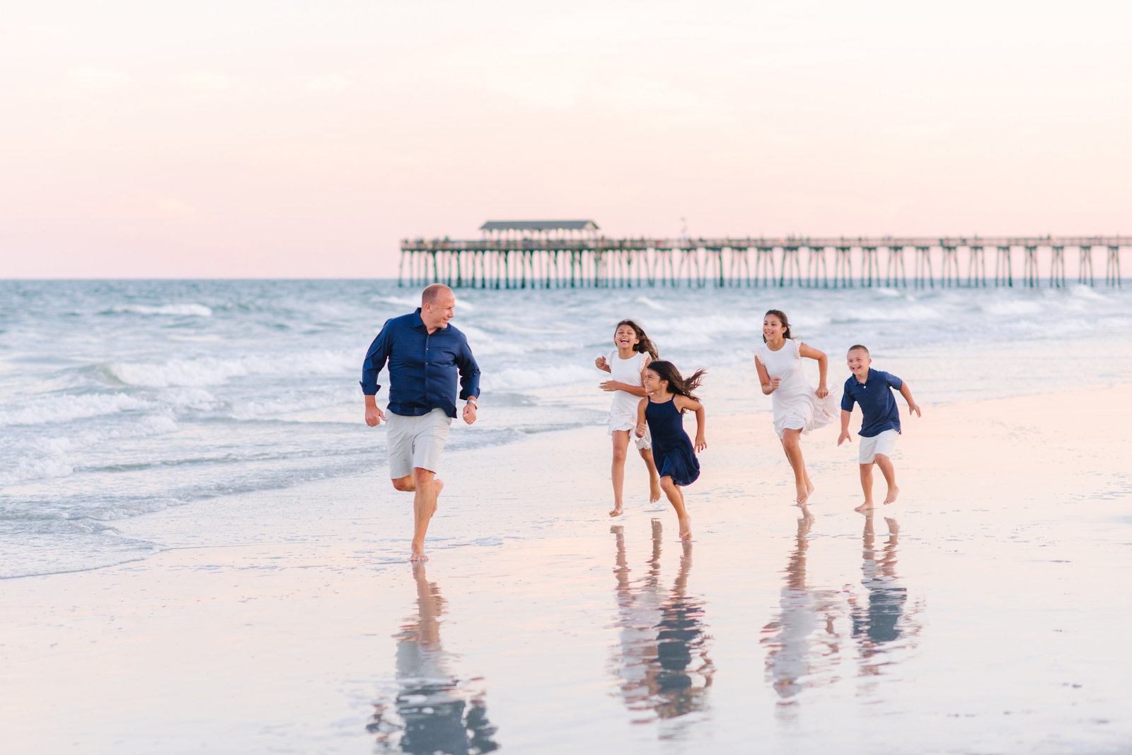 Father and children running on the water - family photography ideas on the beach in Myrtle Beach