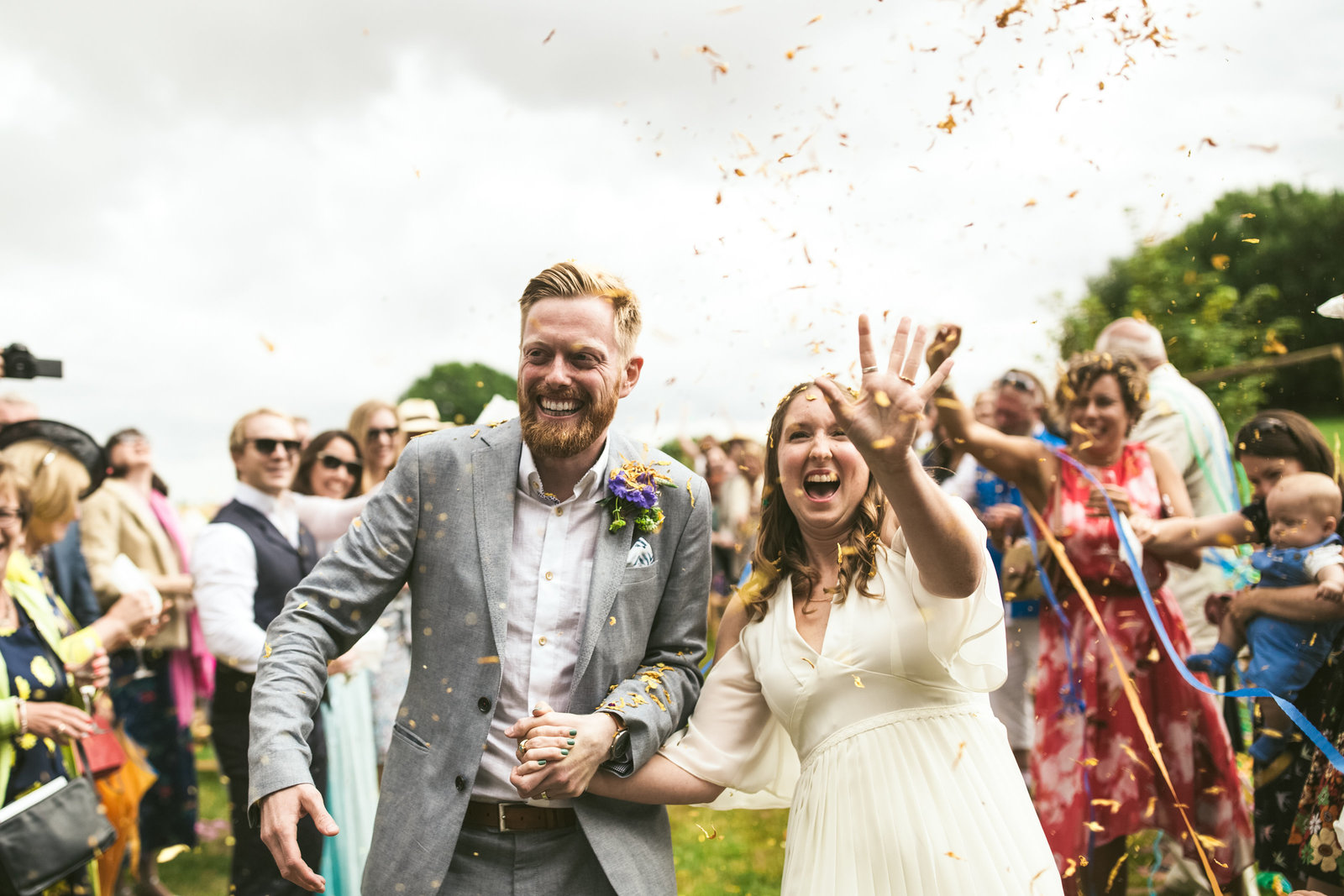 A couple laugh as confetti is thrown at them as they walk down the aisle after their outdoor ceremony in Norfolk.