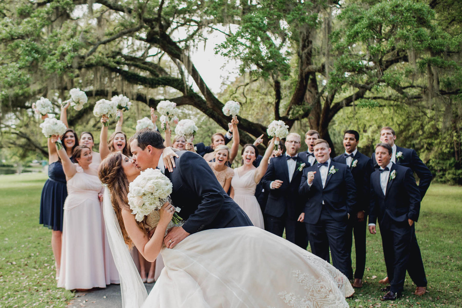 Bride and groom kiss while wedding party cheers, Brookgreen Gardens, Murrells Inlet, South Carolina. Kate Timbers Photography.