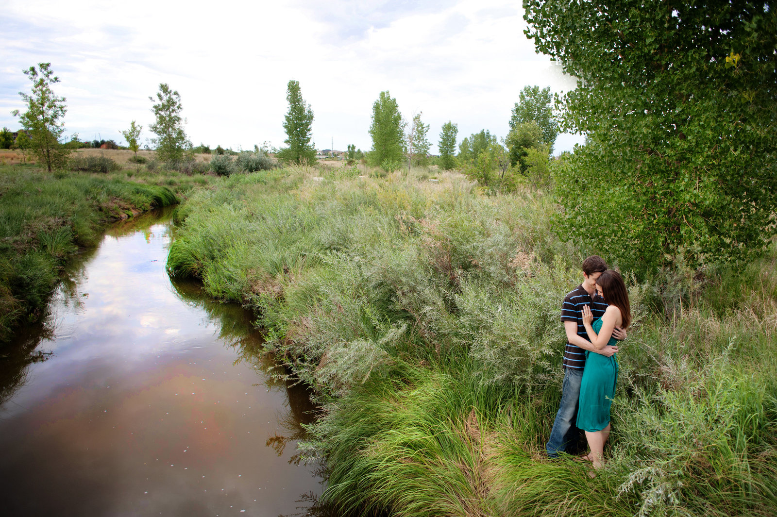 a couple embrace next to a stream in denver