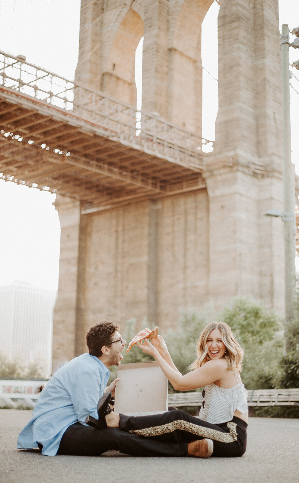 Woman feeding pizza to her boyfriend in front of a bridge while sitting on the ground during their engagement session