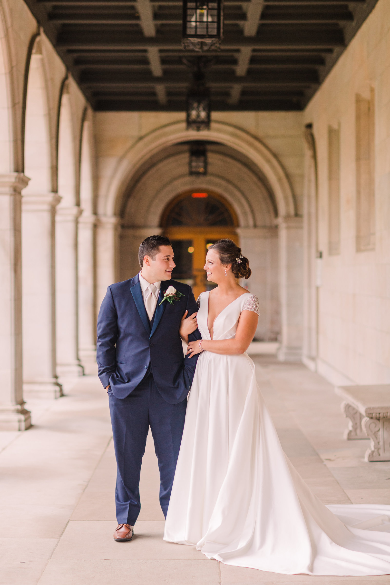 Bride and Groom, Suzie and Ale, stand arm in arm in the great hall of Washington University.