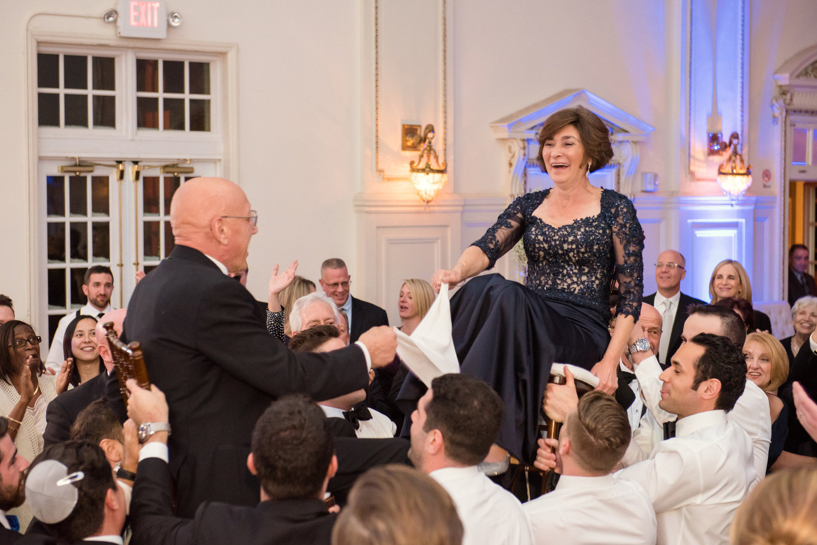 parents on chairs during the Hora at a jewish wedding