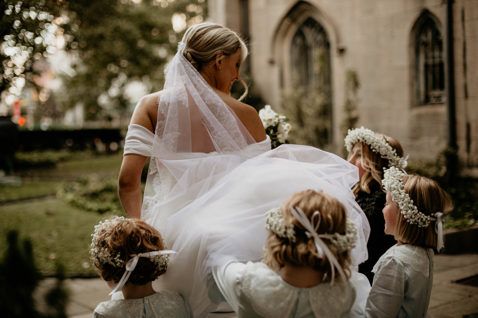 Bride exits Grace Church with flower girls carrying her veil.