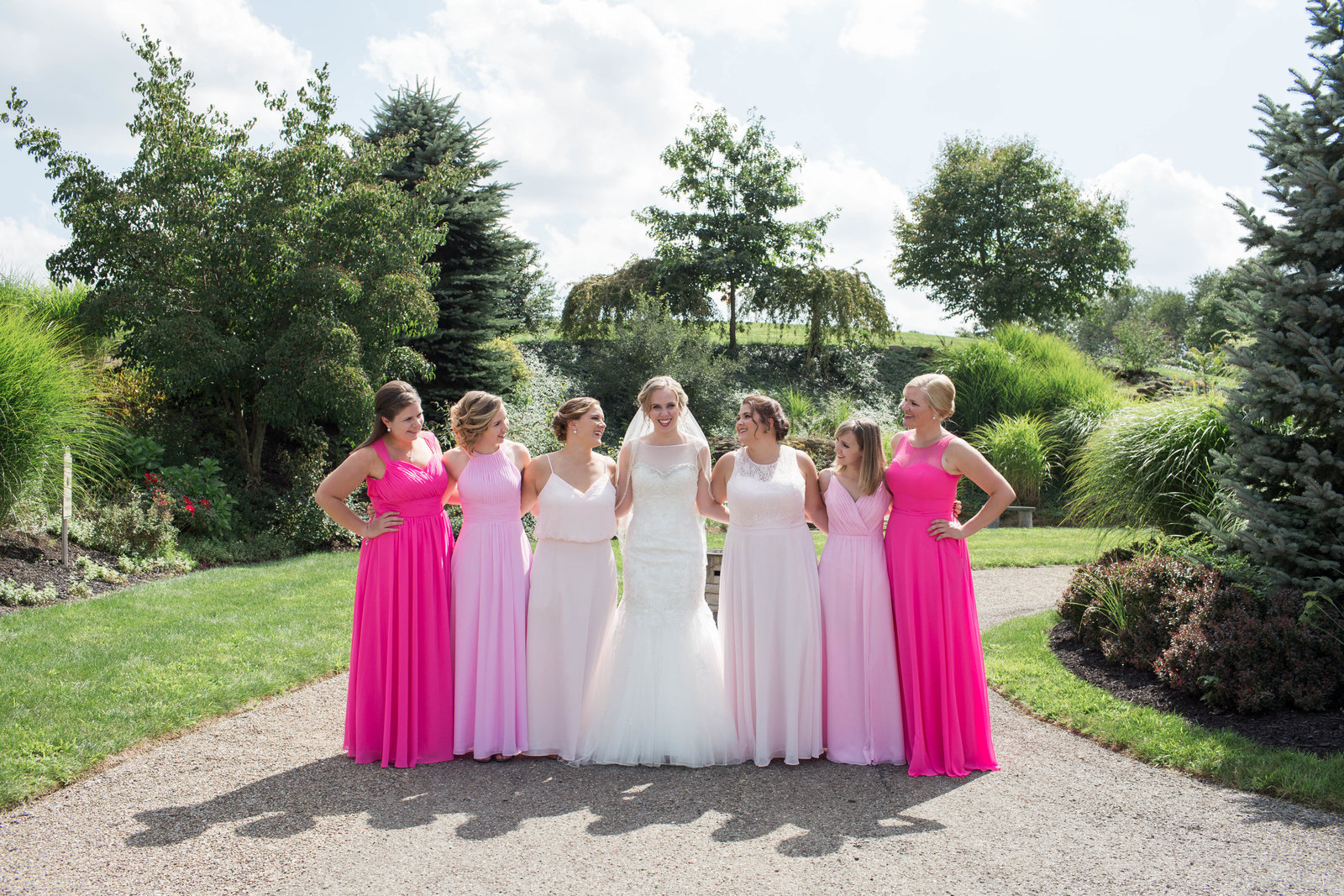 bridesmaids in varying shades of pink line up with bride on a pathway