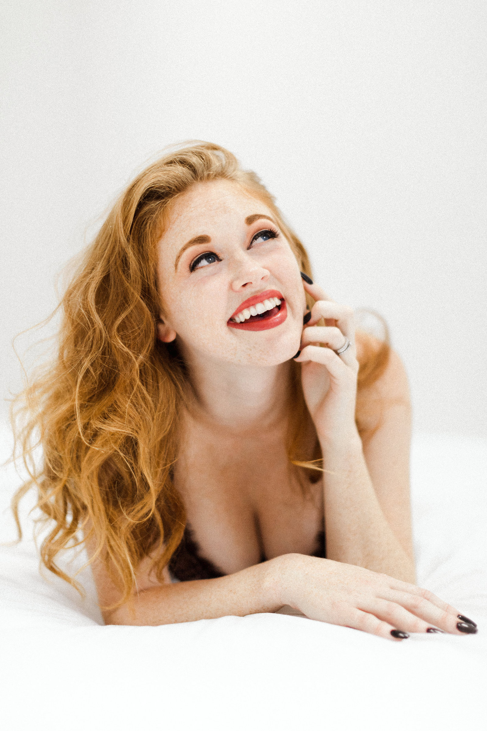 laughing girl red hair lipstick on bed