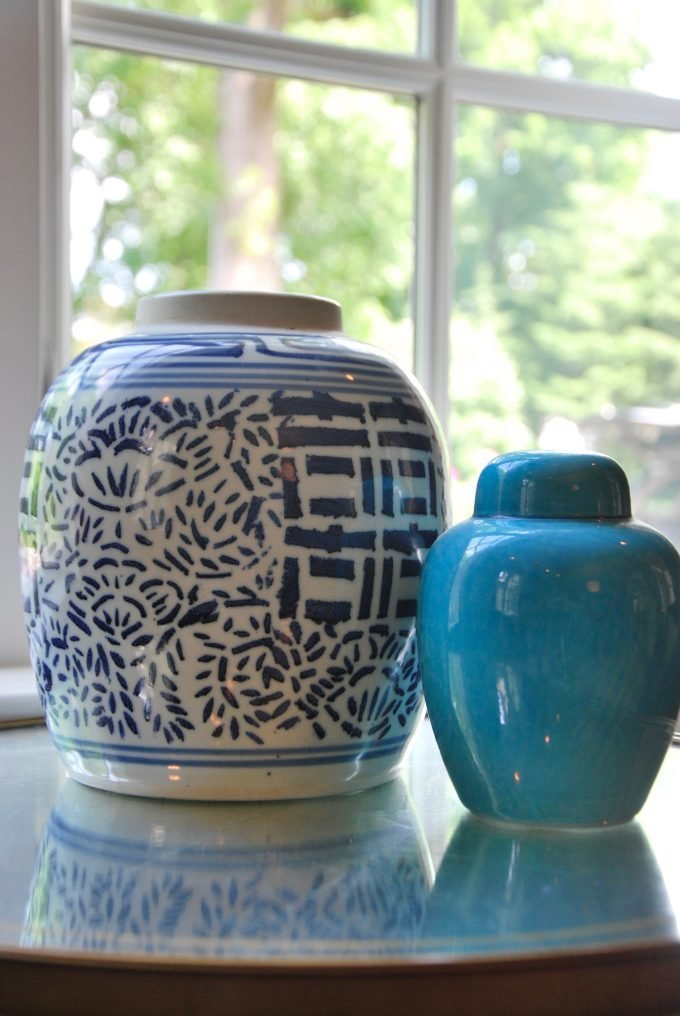 Blue and white, and turquoise ceramic vases on a glass accent table.