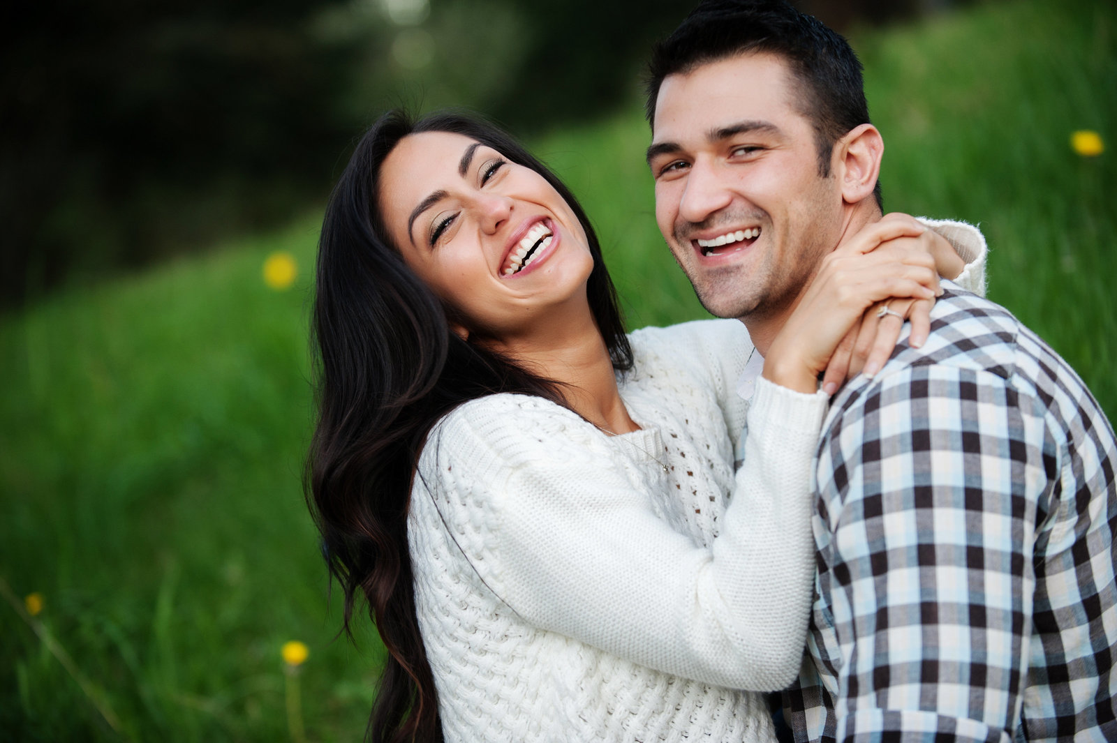 an engaged couple laughs in the grass