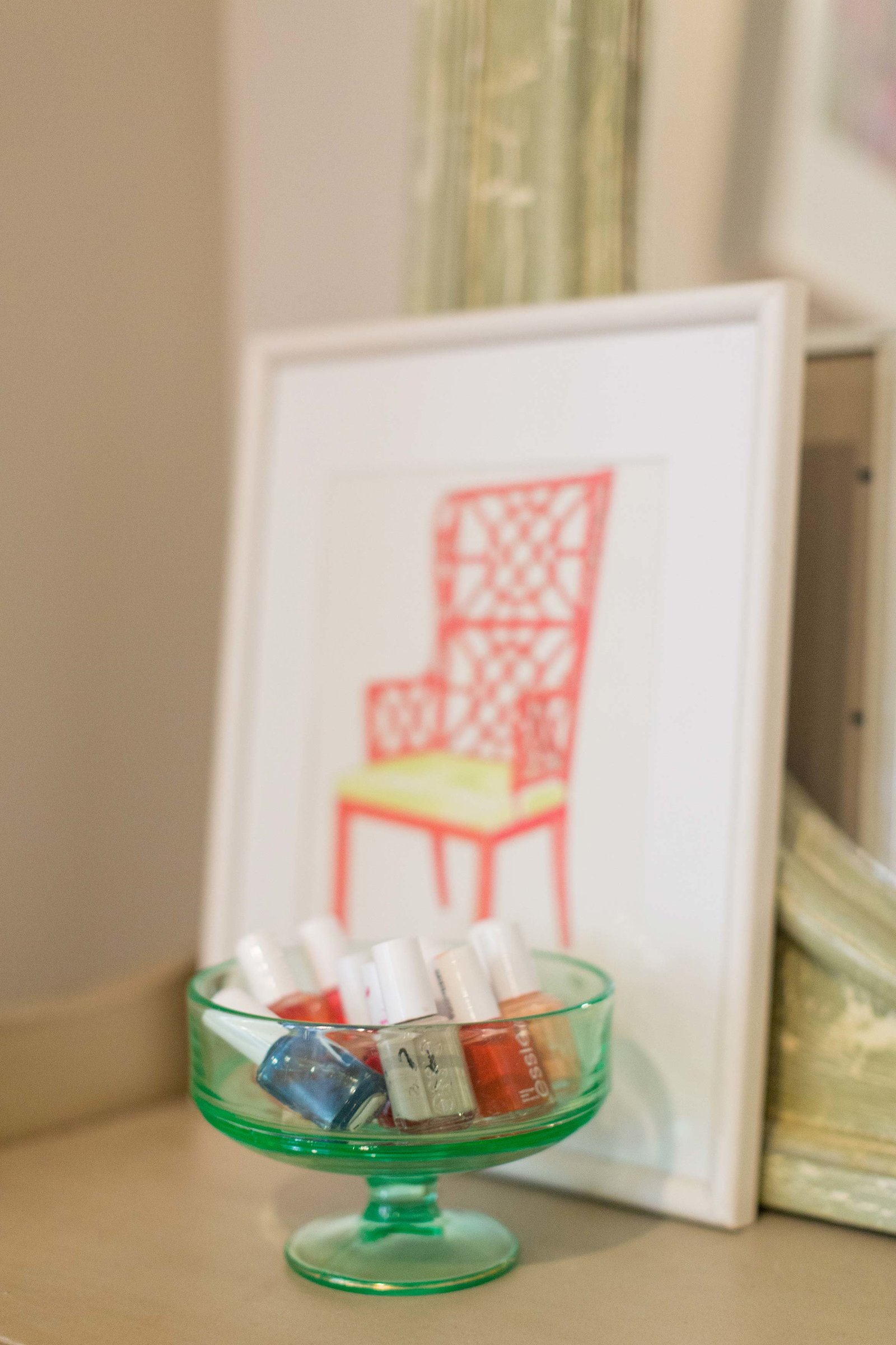A glass dish with nail polish and a framed print of an orange chair.