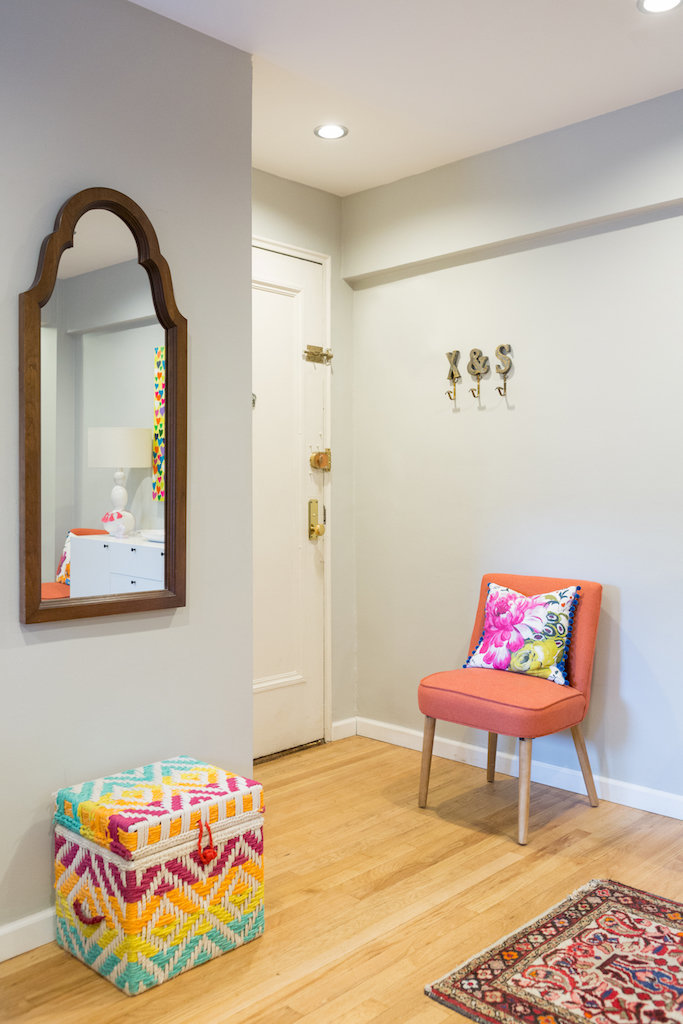An entry way with an orange chair, colorful basket, hooks, and a mirror.