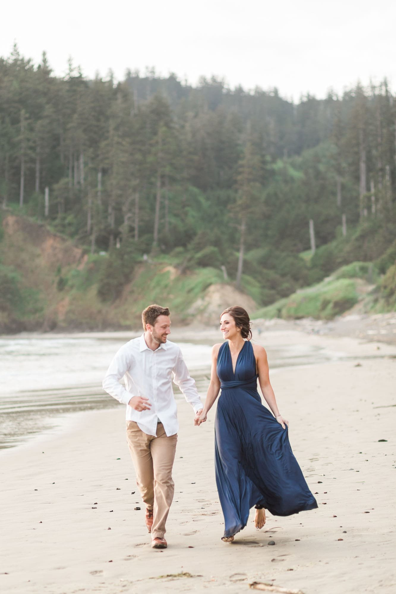 Couple holds hand during Cannon Beach engagement photos