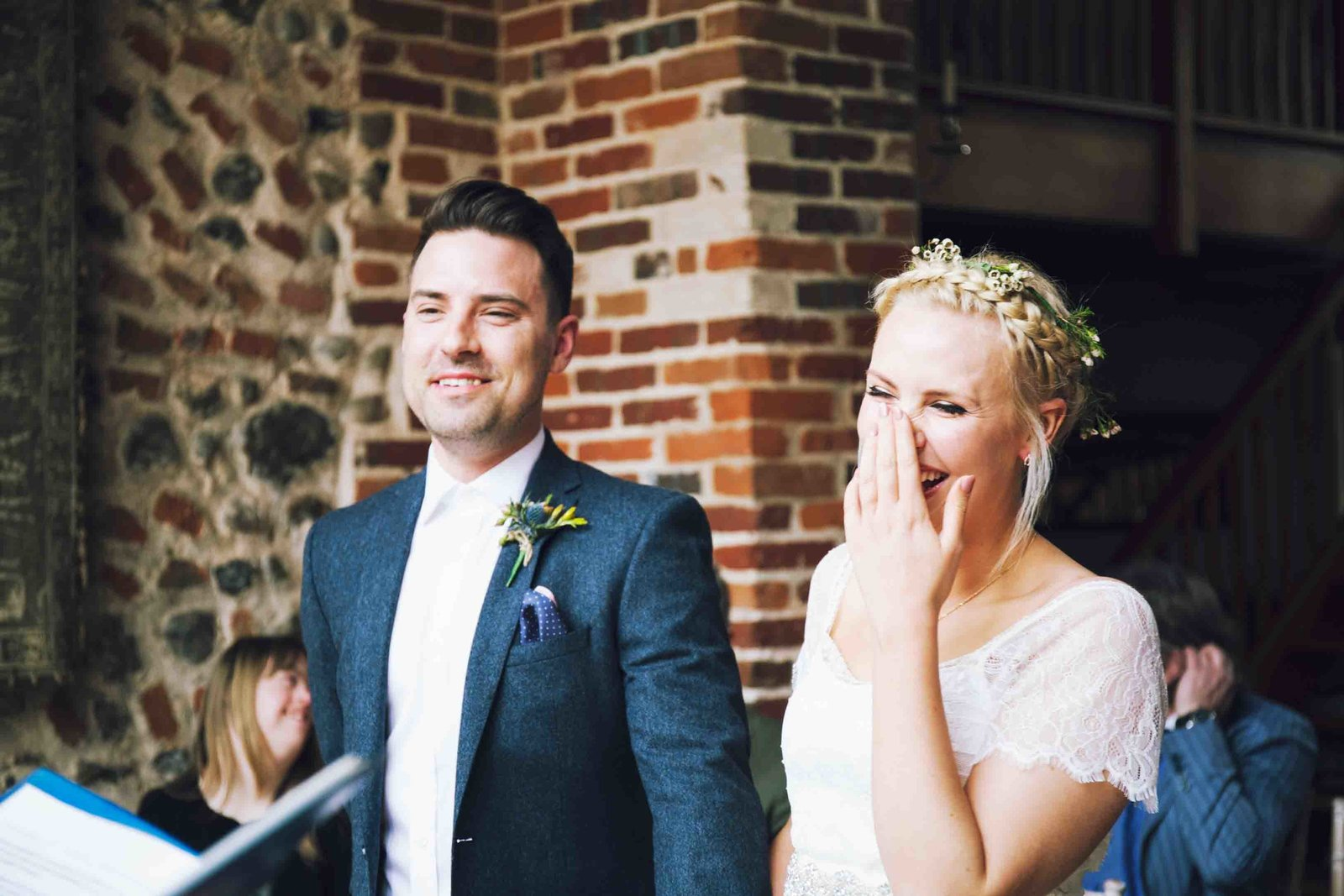 Relaxed laughing bride and groom during their ceremony vows  at Chaucer Barn wedding in Norfolk