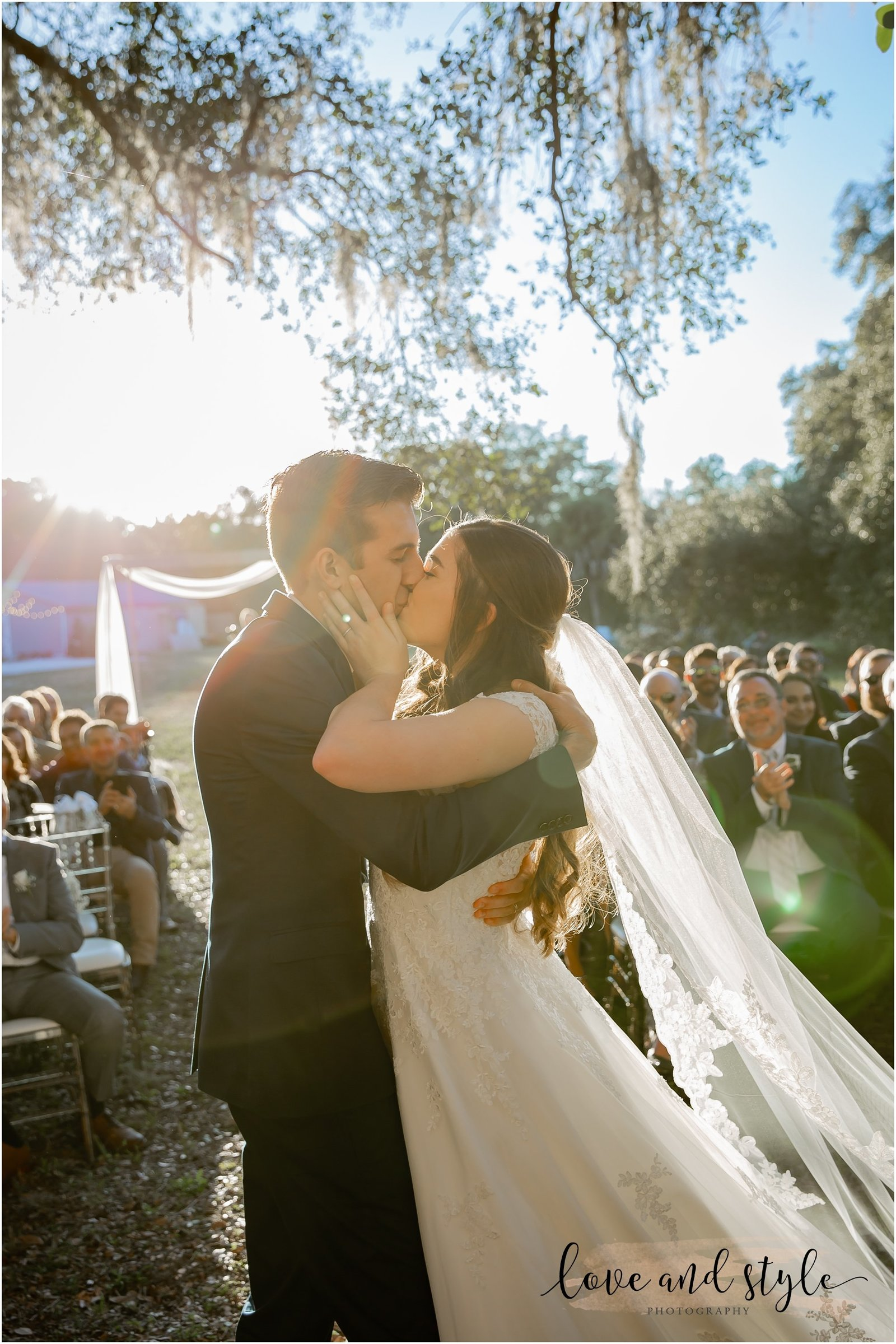 Bride and Groom kissing for the first time as husband and wife after the ceremony at The Barn at Chapel Creek Wedding venue in Venice, Florida