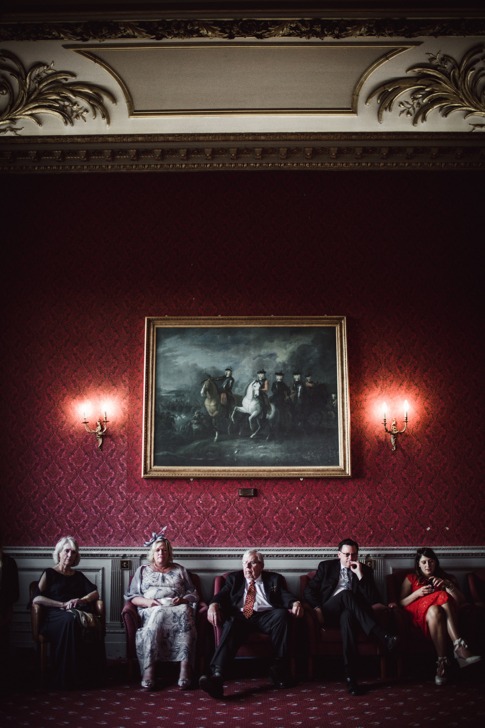 Elderly wedding guests sit side by side under a large oil painting in a red drawing room in a stately home in Norfolk.