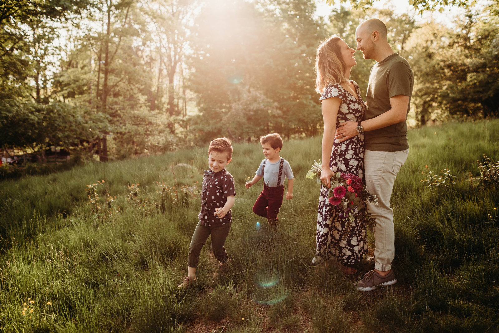 little boys run around their parents in a sunset field for boston family photos