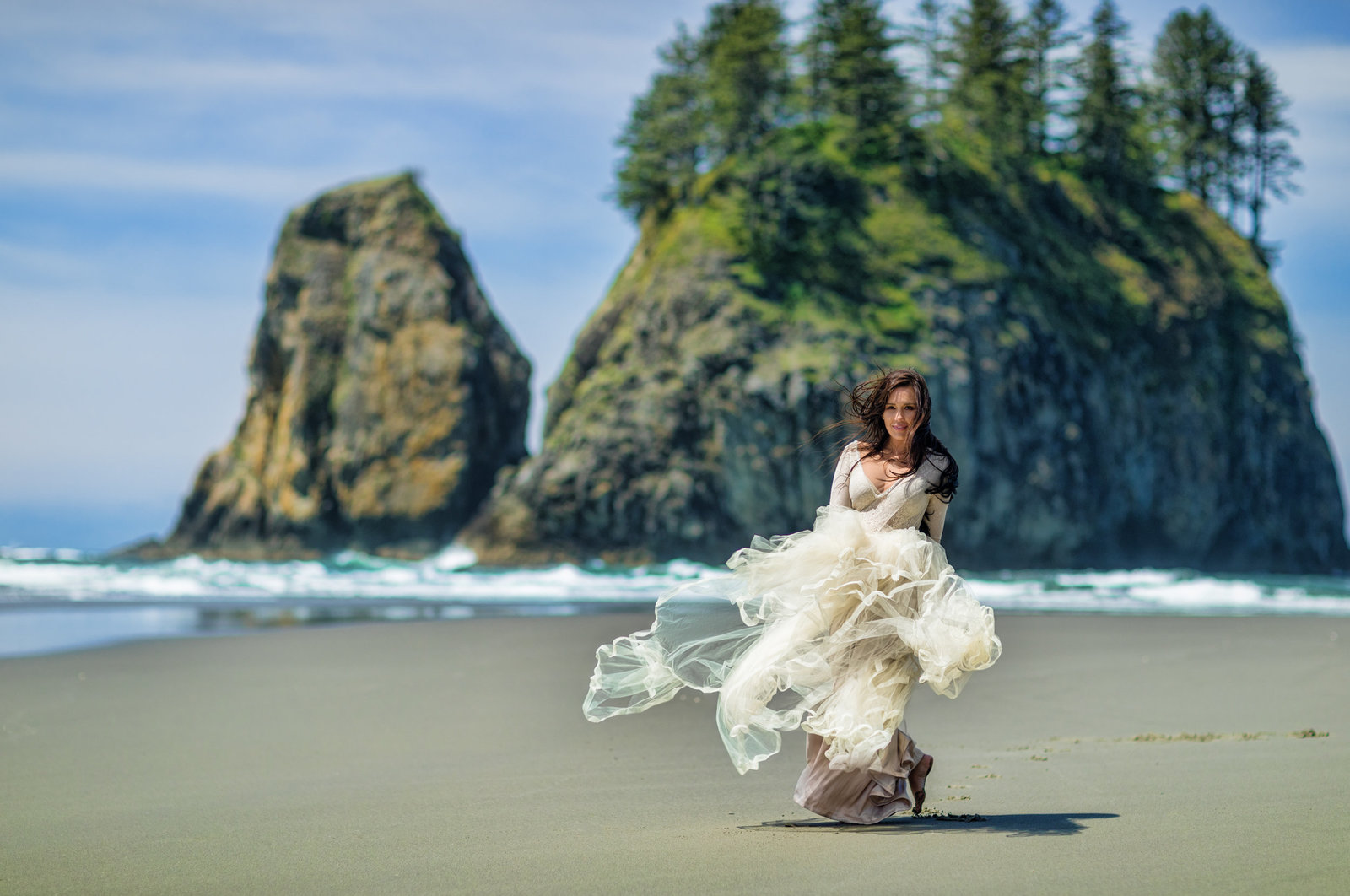 Bride walking on beach enjoying the wind