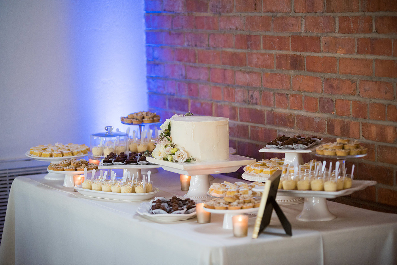 beautiful photo of reception room at brick dessert table