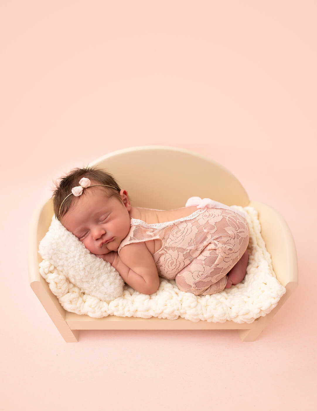 Sleepy newborn posed on a small couch in our Rochester, NY studio.