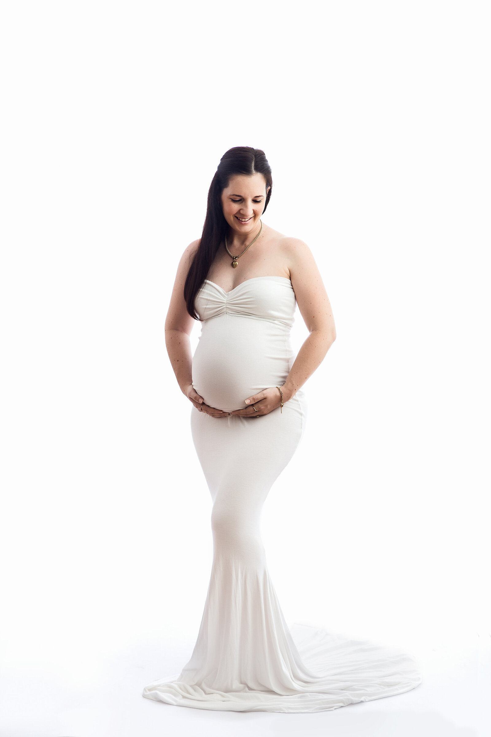 Professional maternity portrait in-studio, pregnant lady in long white dress