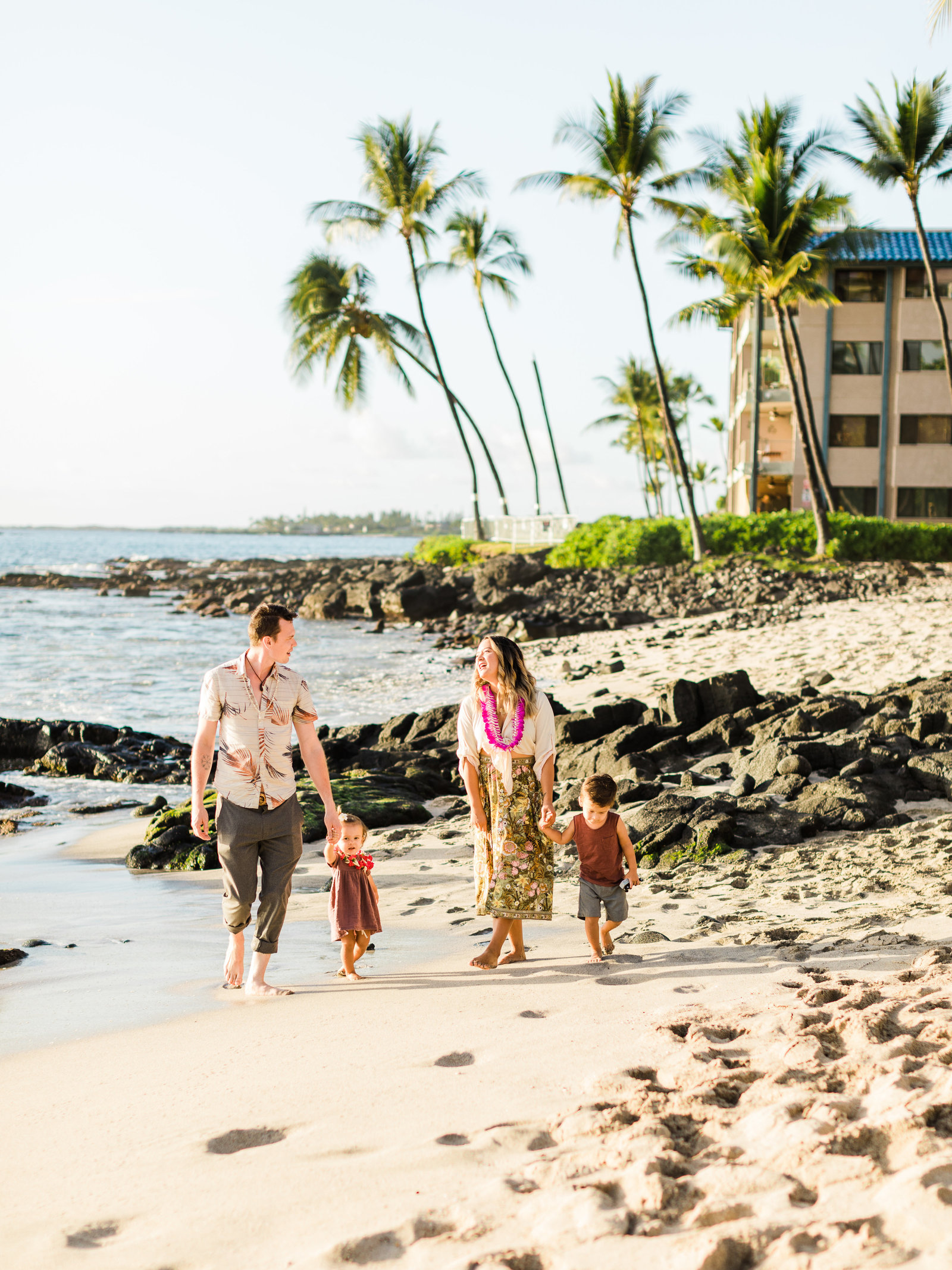 Young couple walk on a beach in Hawaii with their two young children, surrounded by lava rocks and palm trees while wearing leis