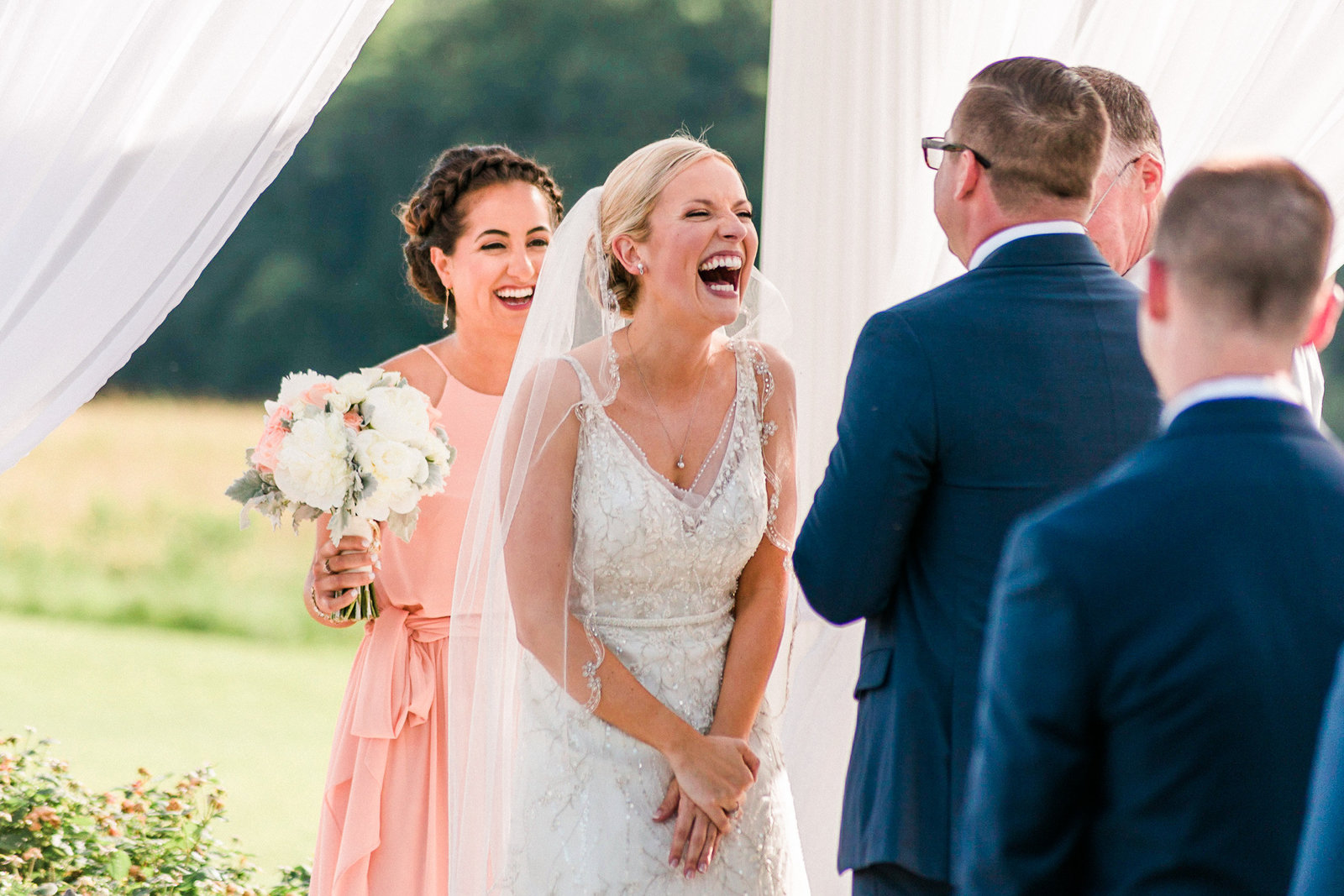 Bride laughs at her wedding ceremony, surrounded by white curtains at Springfield Manor Maryland