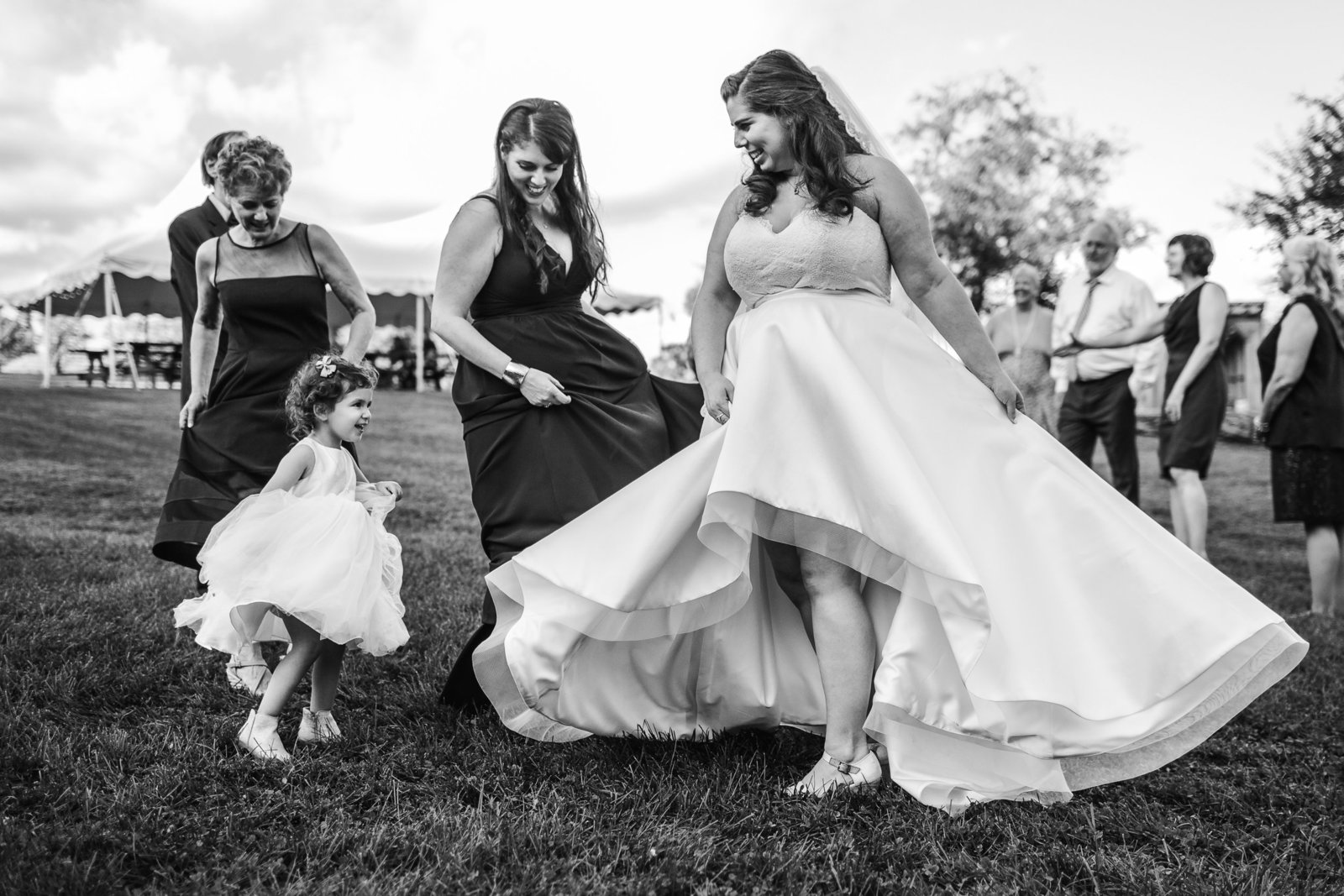 bride spins dress with flower girl outdoors in massachusetts
