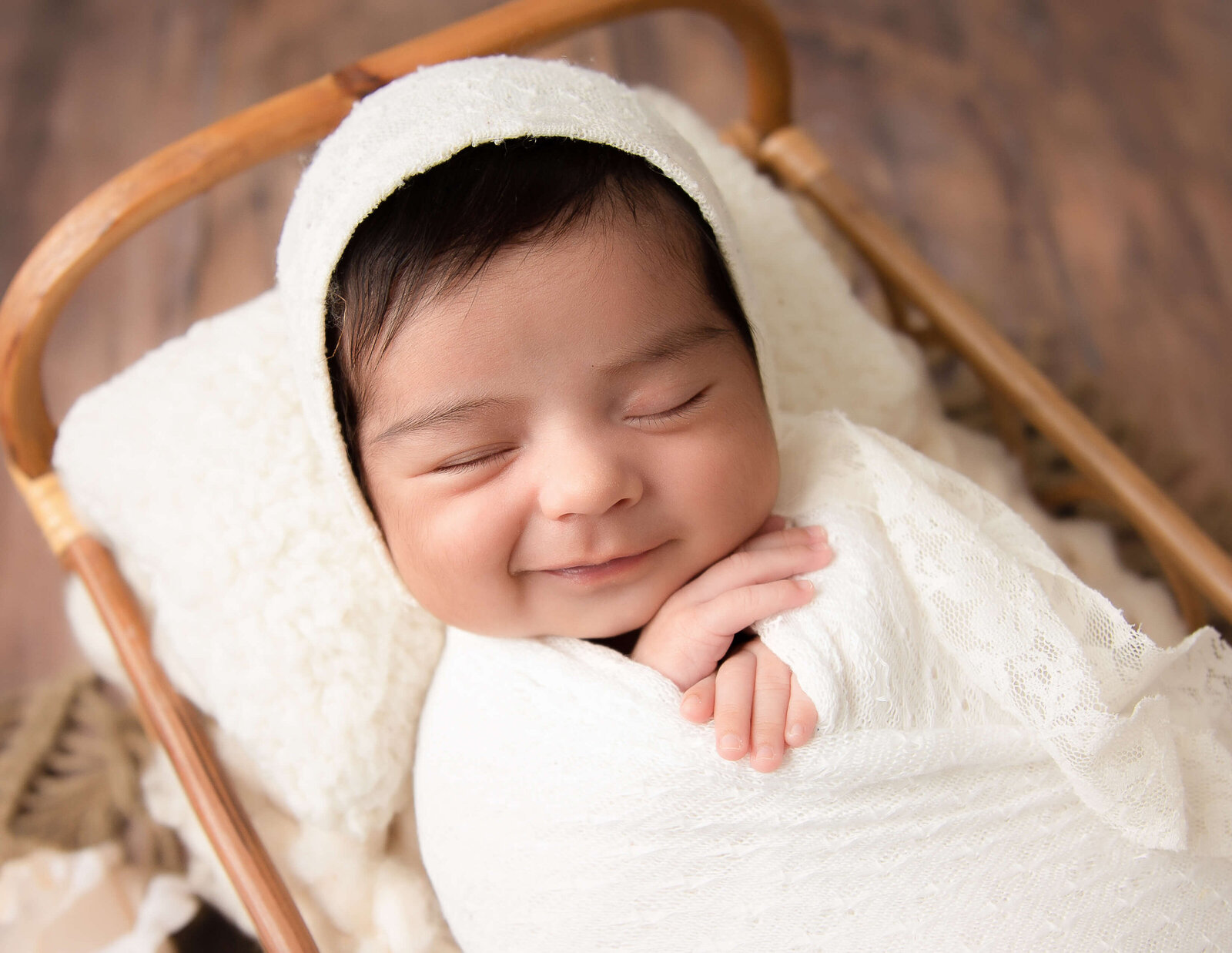 Smiling newborn girl at our in-home Rochester, NY studio.