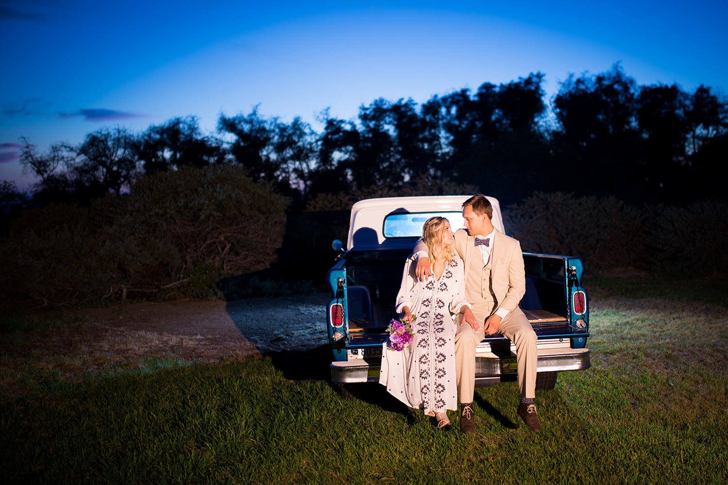 rustic blue truck with bride and groom sitting