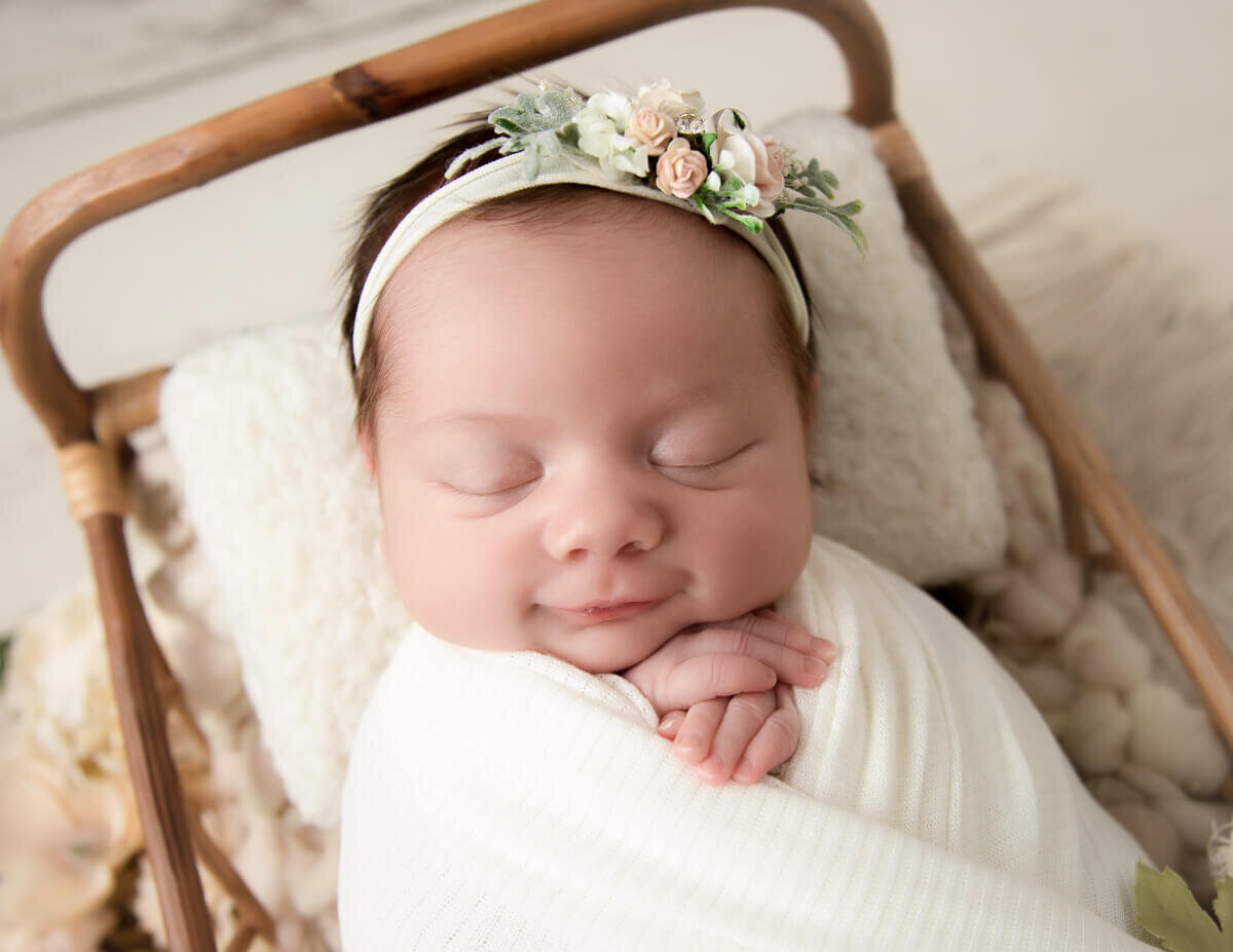 Smiling newborn girl posed at our in-home Rochester, NY studio.