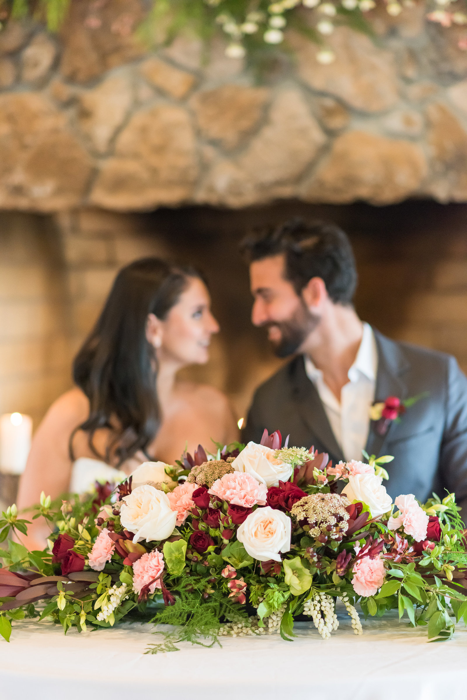 Bride and groom behind a burgundy and blush sweetheart table arrangement