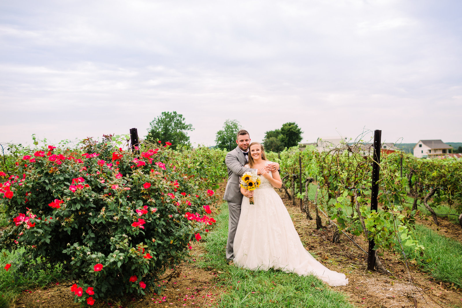 Bride and Groom, Whitney and Derik, pose in the vineyards with flowers to the side and a clear blue sky at Chaumette Winery.