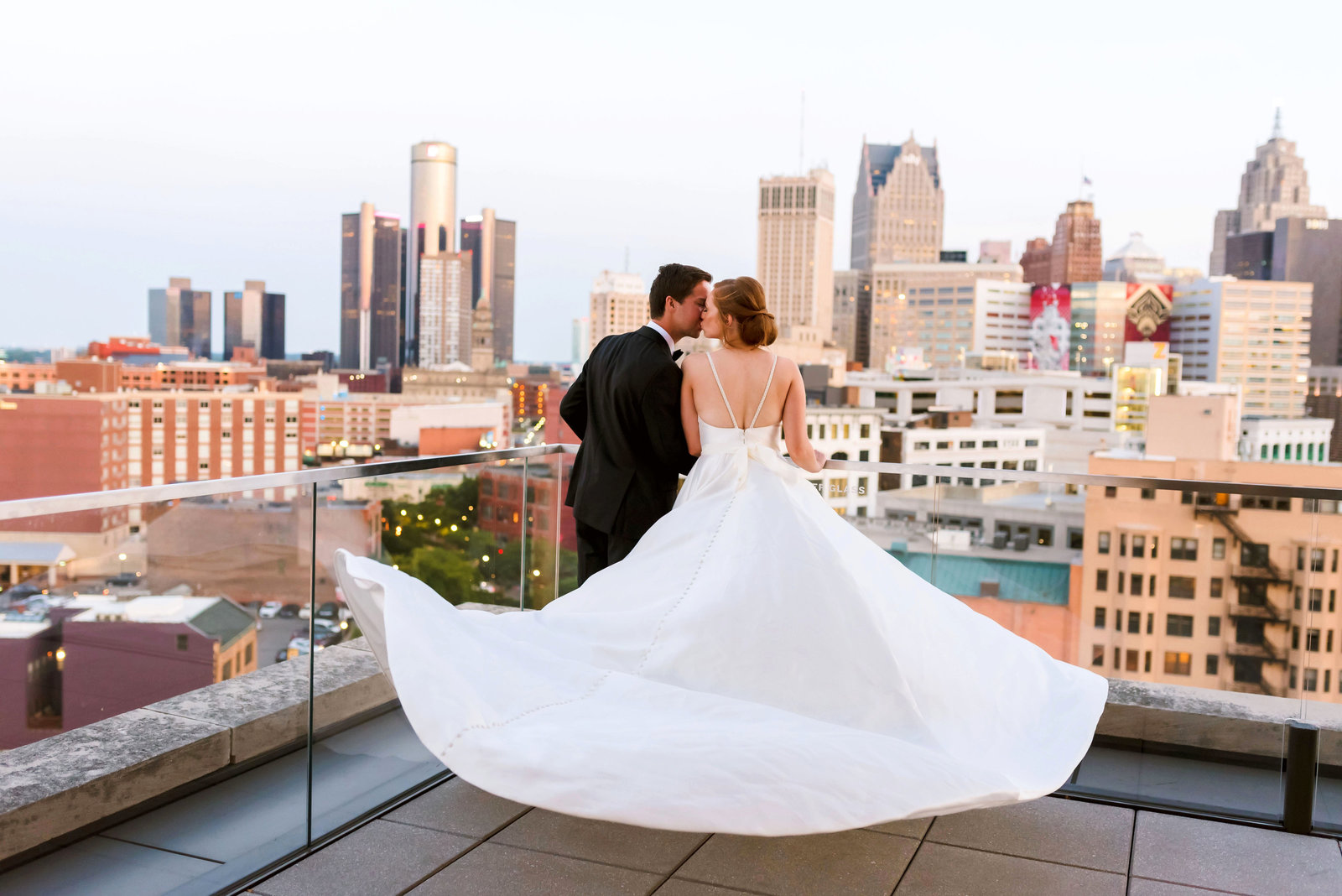Wedding photo of a bride and groom on the roof of the DAC with the Detroit skyline