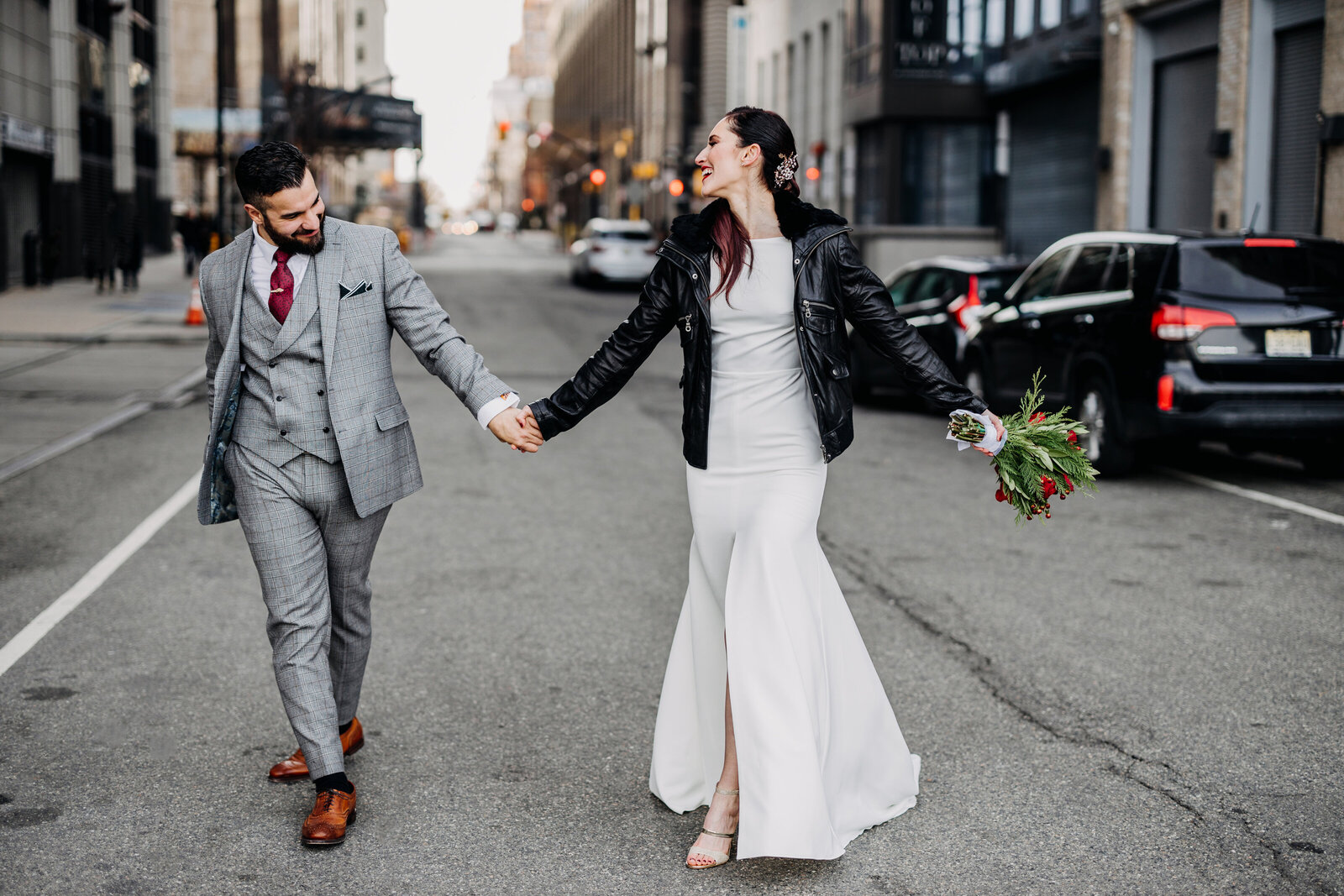 bride with leather jacket and groom walking down city street