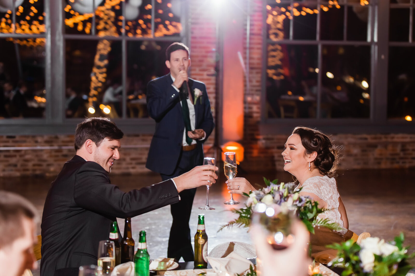 Bride and groom clinking glasses during toasts at their wedding reception at NEO on Locust in STL