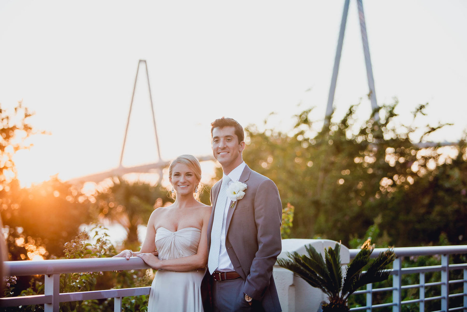 Bride and groom pose at sunset with Ravenel Bridge in background, Harborside East, Mt Pleasant, South Carolina