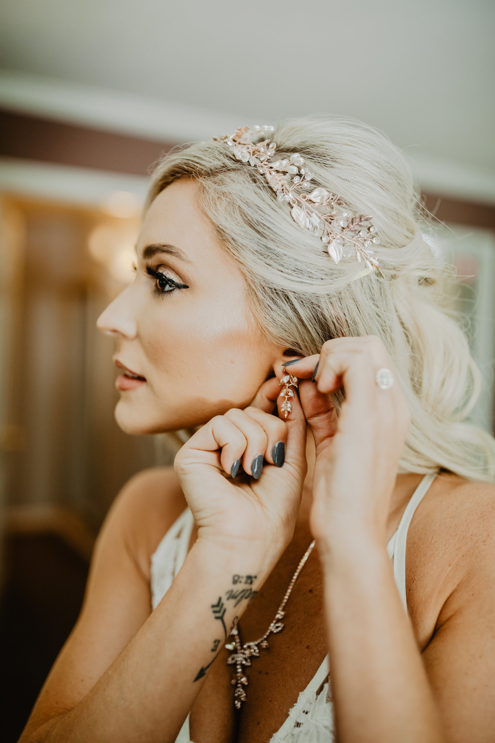 A brides accessories are not complete until she puts on her earring for her intimate backyard wedding