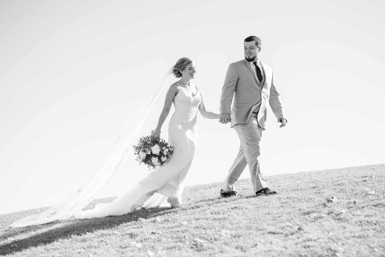 Black and White image of bride and groom walking up a hill in daylight.