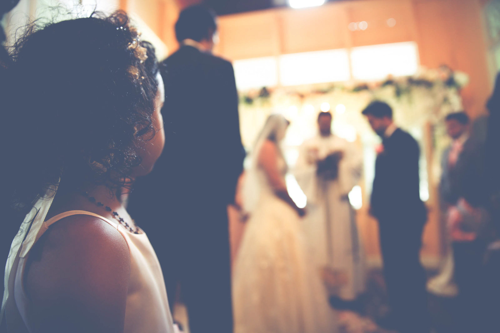 Little girl looks on as bride and groom get married. Photo by Ross Photography, Trinidad, W.I..