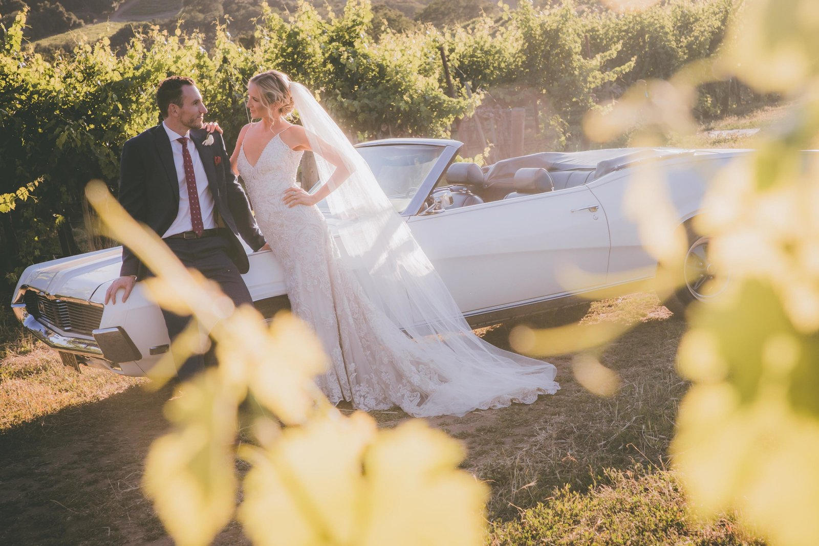 Groom and bride pose against white car in vineyard.