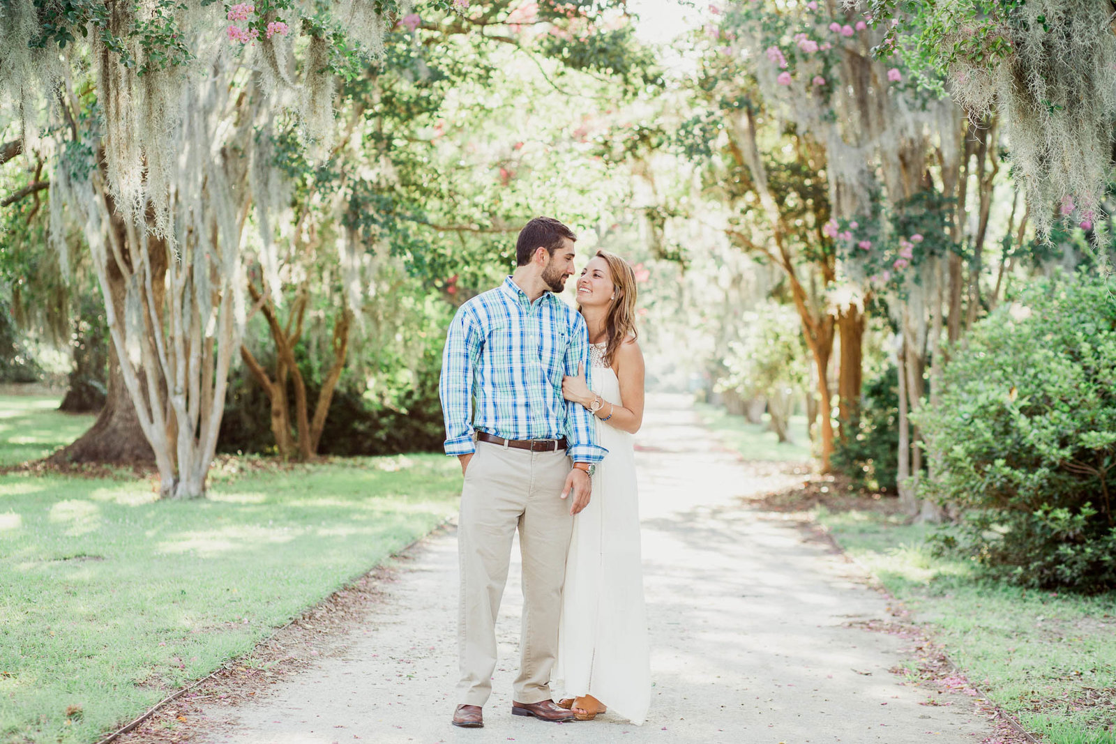 Engaged couple stands in clearing with spanish moss covered trees all around, Hampton Park, Charleston, South Carolina