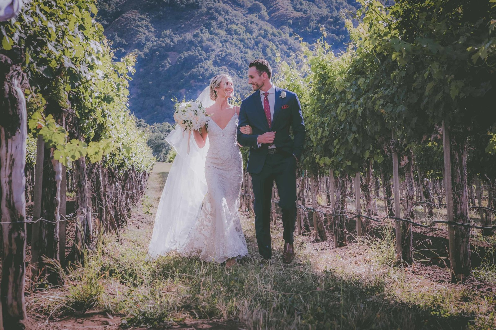 Bride and groom walk and laugh among a Carmel Valley vineyard.