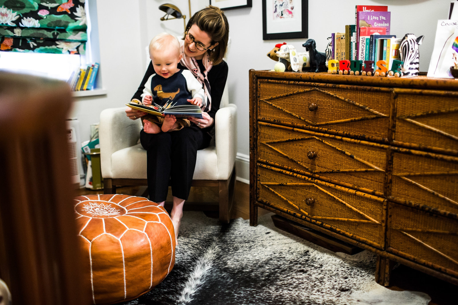 Mom reading book to her son in trendy eclectic apartment