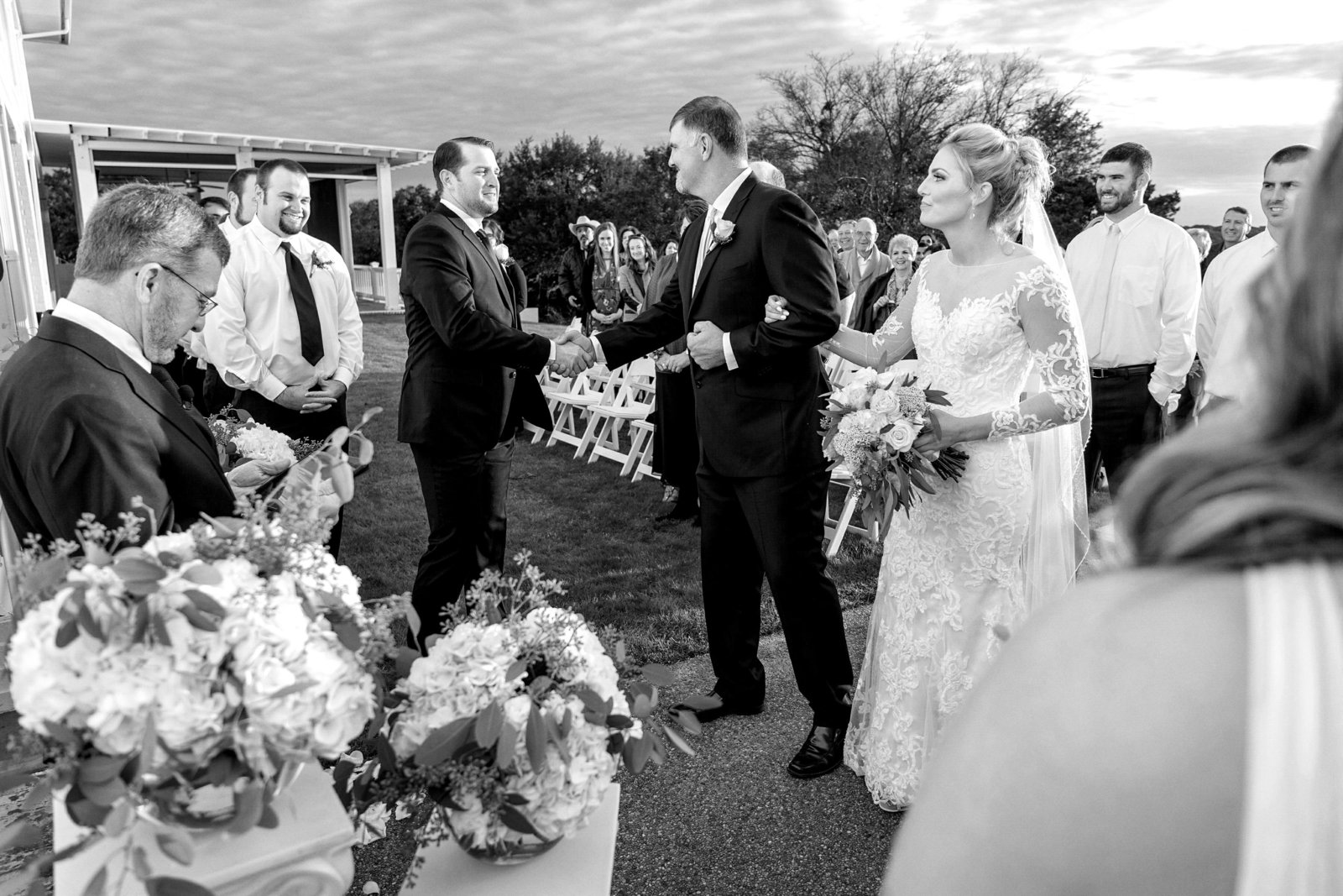 Groom shanking father of the brides hand during ceremony at pecan plantation country club in granbury texas