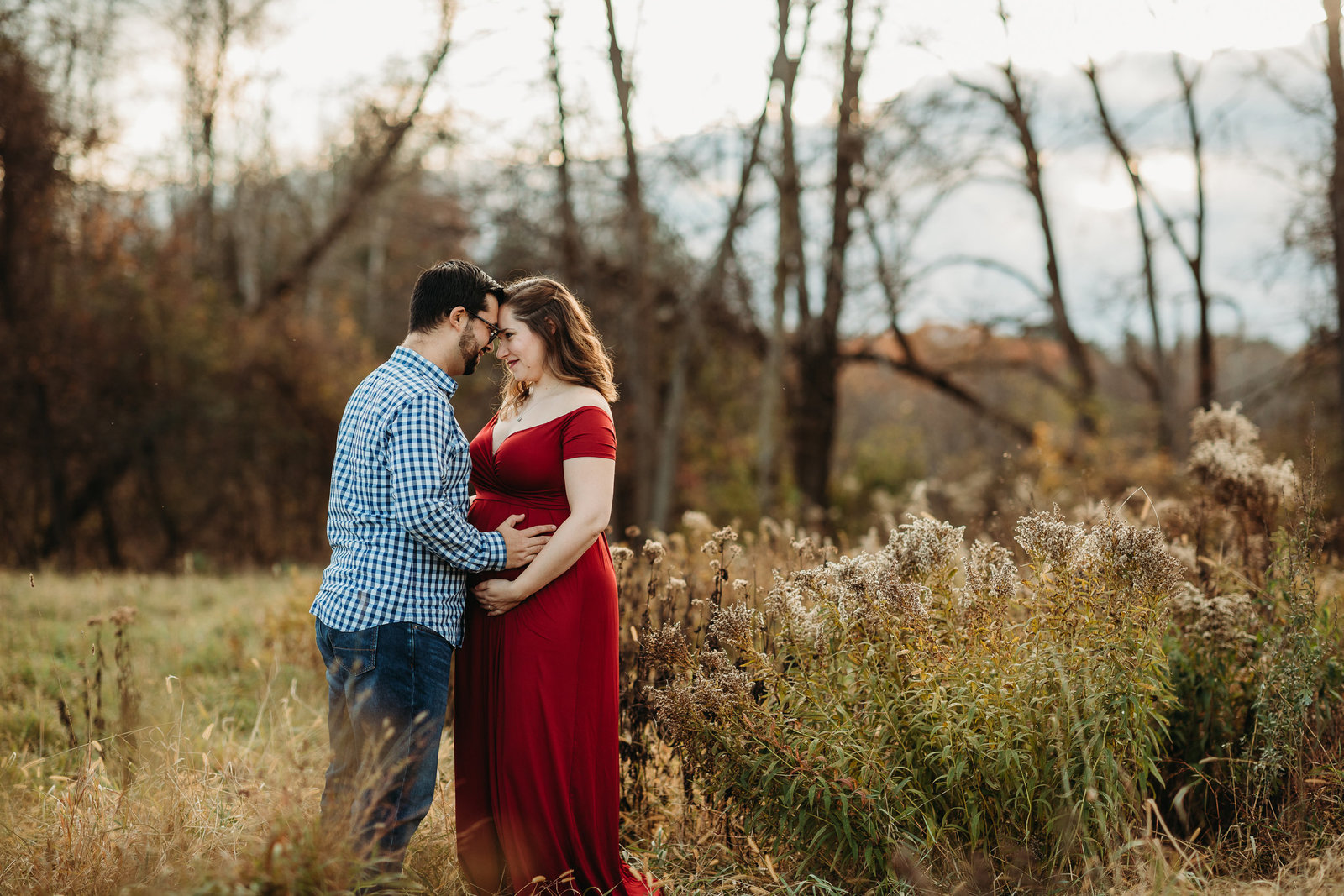 pregnant couple in red dress go forehead to forehead in field in framingham ma