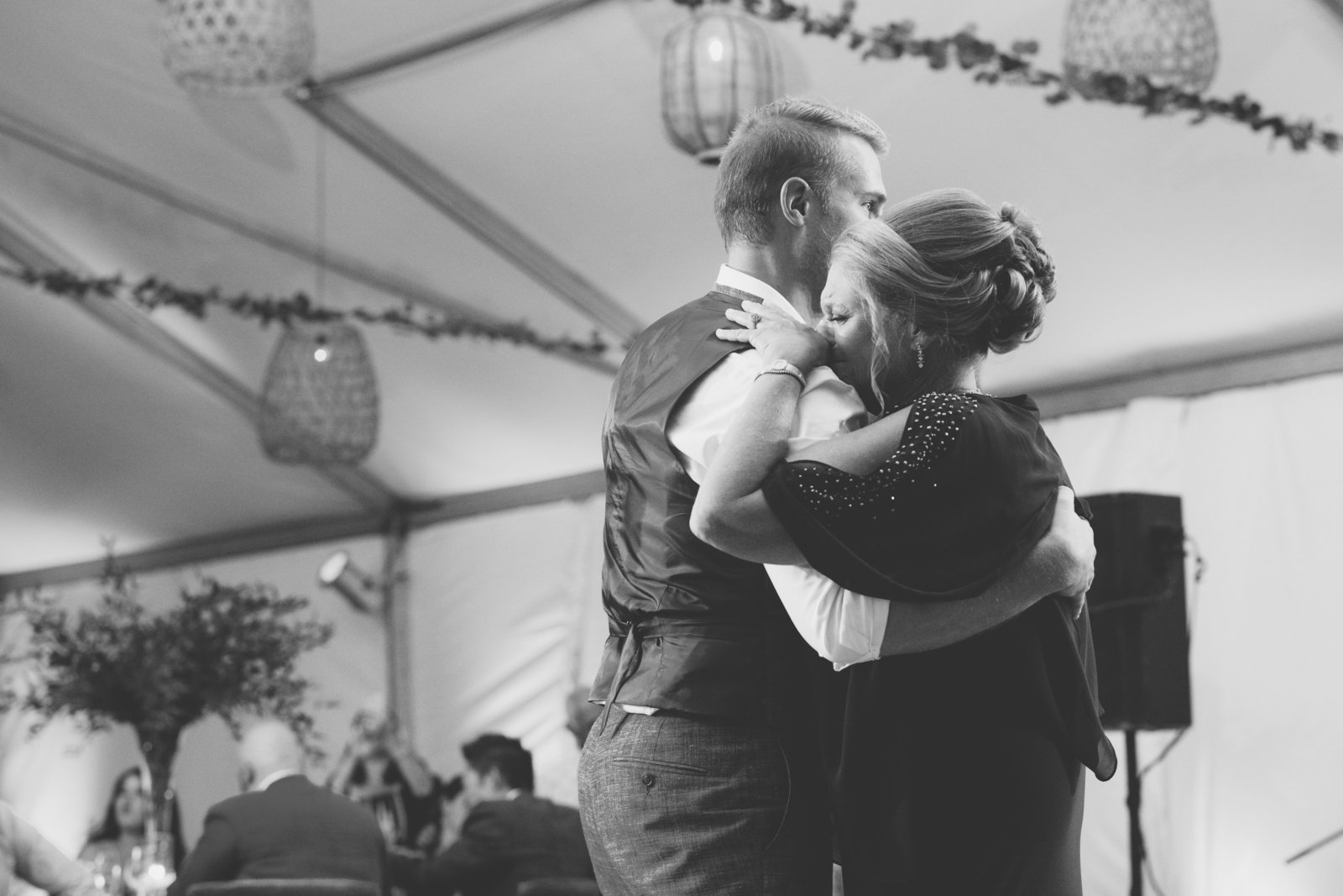 black and white photo of groom dancing with crying mom at Gurneys Montauk Resort wedding