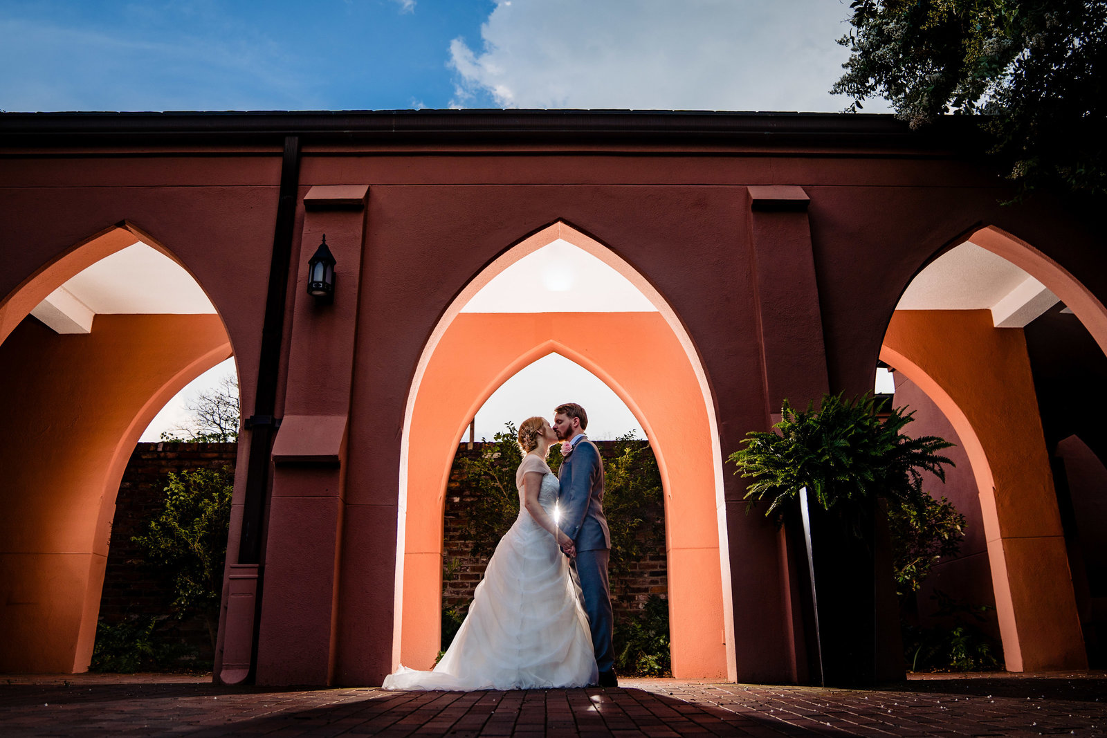 bride and groom standing under arches