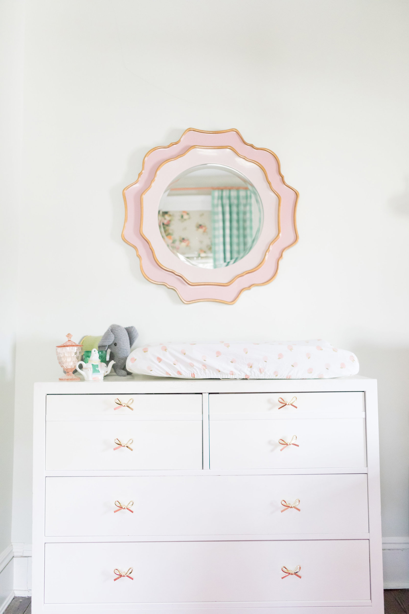 A white dresser with bow pulls and a round mirror.