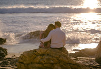Newly engaged couple embraces on shoreline rocks