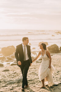 Bride and groom running hand in hand on the  beach at Dana Point